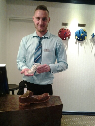 Estoria, Tallinna, hotellivirkailija Fred esittelee johtajan muotoilemia kenkiä