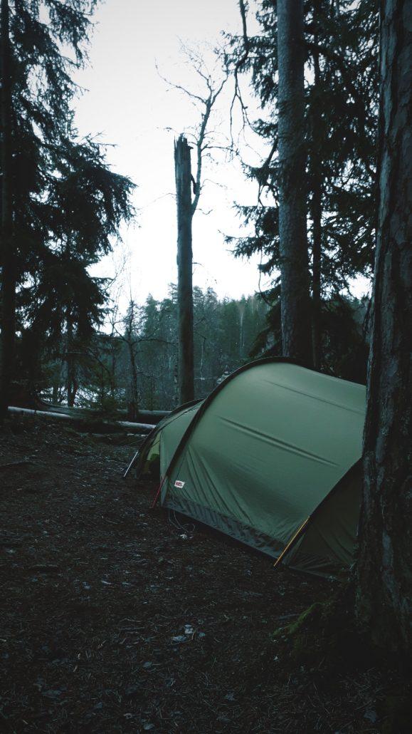 Vihreä teltta puiden katveessa
