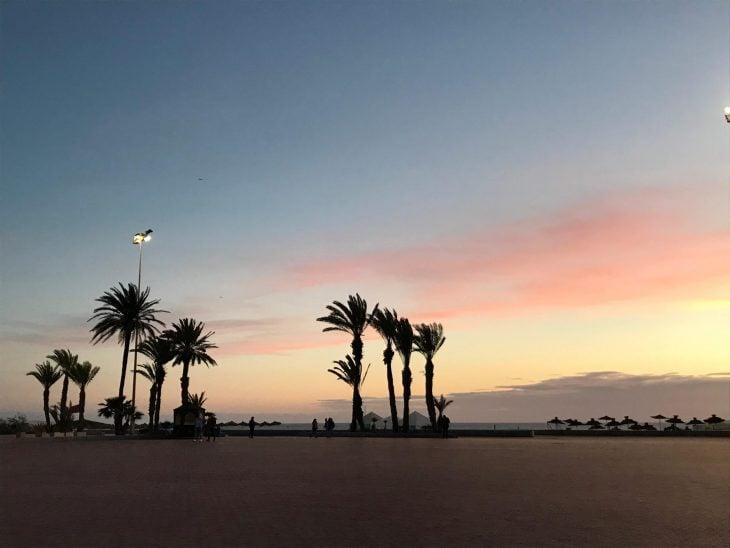 Marokko, Agadir ranta ja palmut auringonlaskun aikaan, nähtävää aukiolla rantabulevardin varrella, hyviä ravintoloita