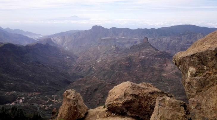 Kivimöhkäleen vieressä on maisemat kohdillaan... Kaukana horisontissa näkyy pilvien joukossa naapurisaaren tulivuoren huippu