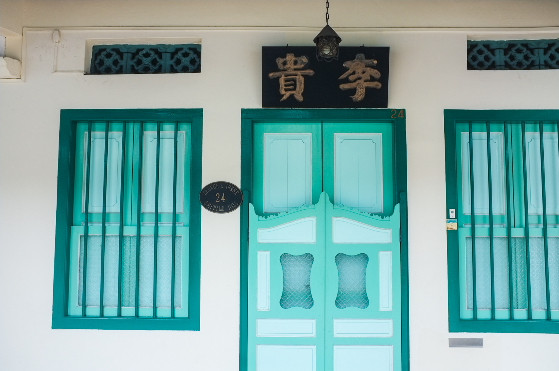 Valkoinen talo jossa on sinivihreät ovet ja ikkunat