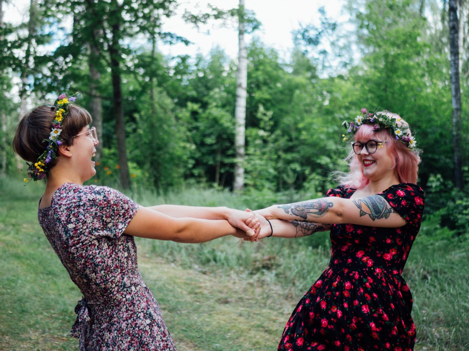 kaksi tyttöä pyörii kesällä kukkaseppeleet päässä. kuva henrietta soininen