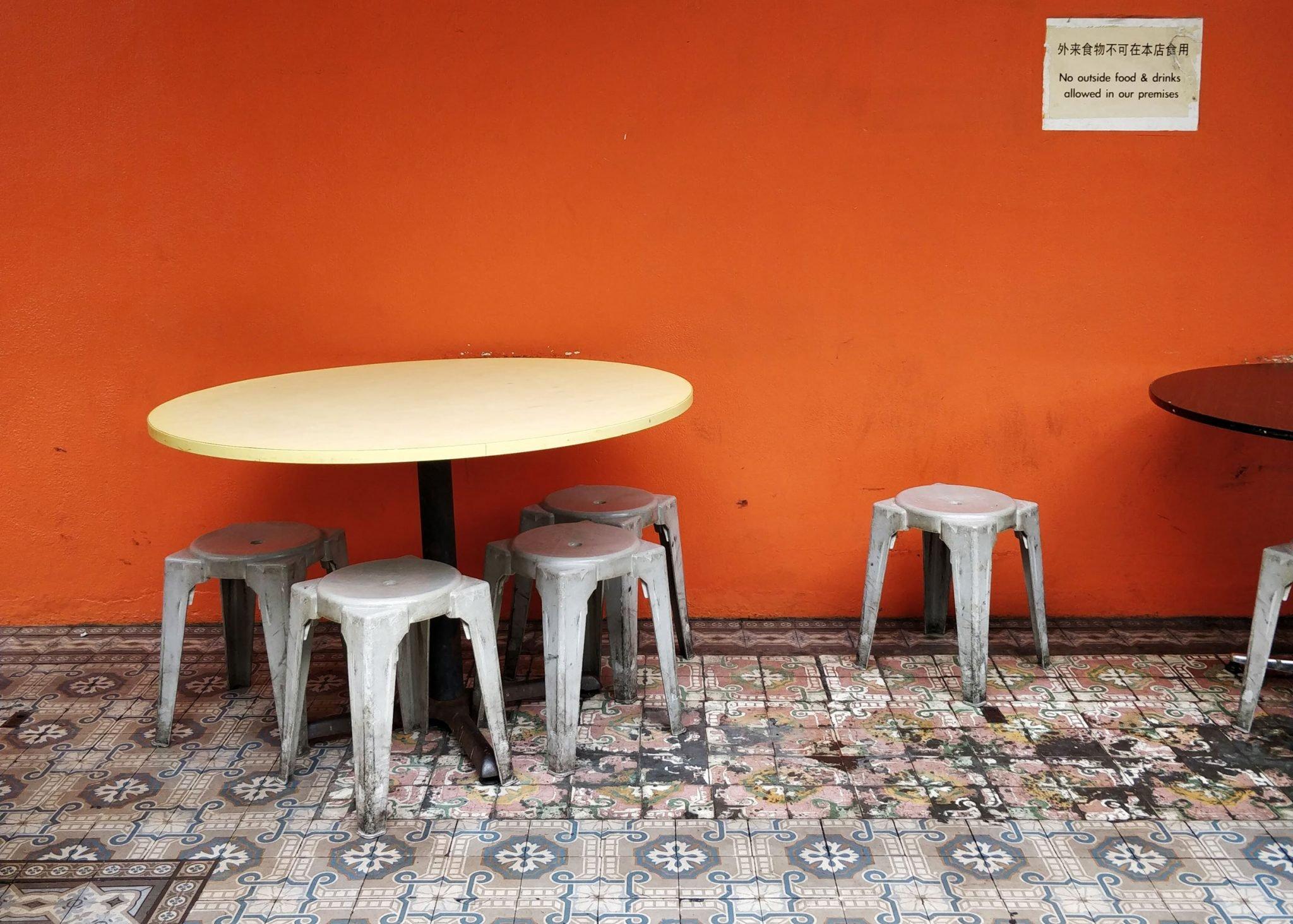 oranssi seinä, laattalattia, pöytä ja tuoleja