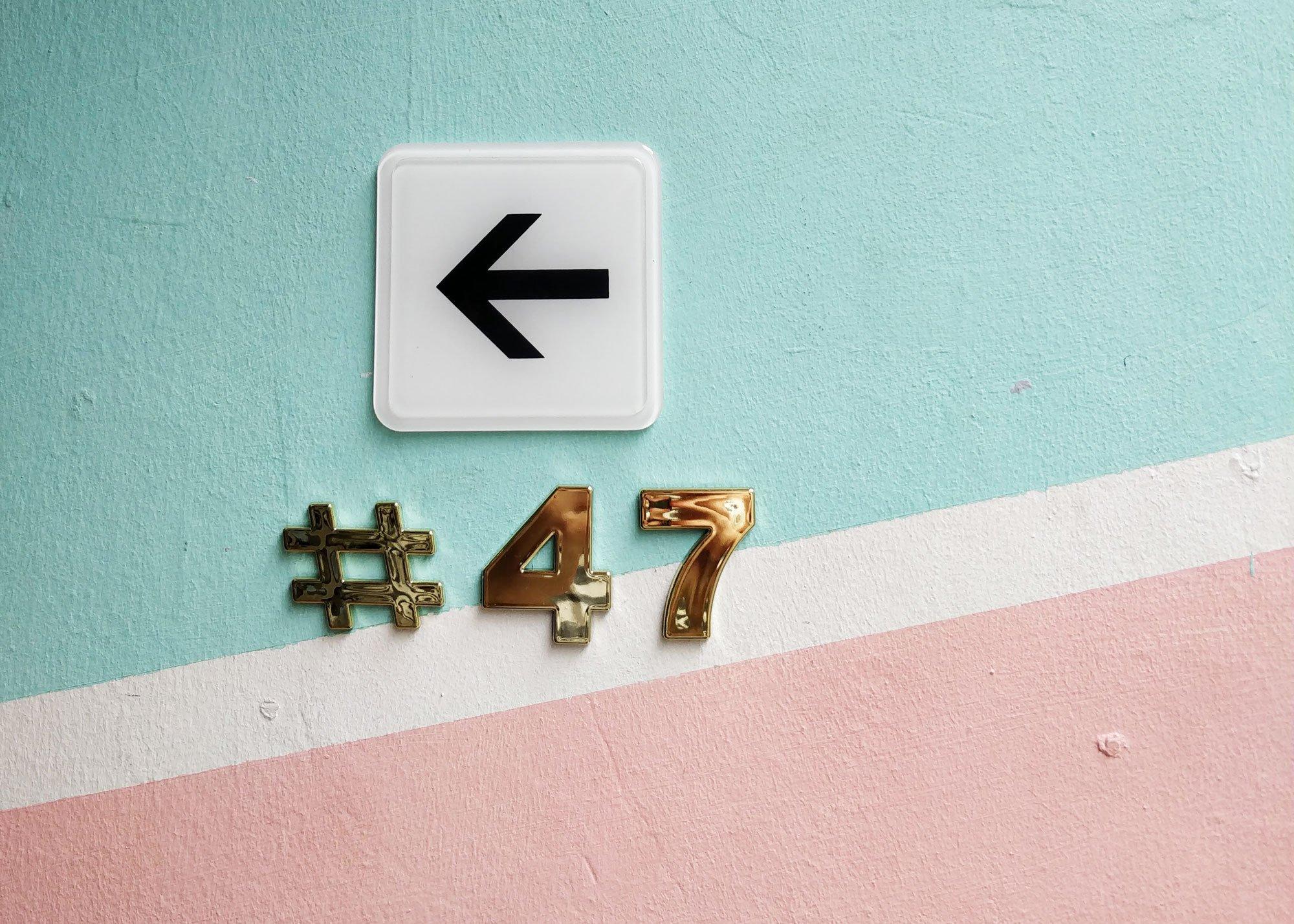 Talon pastellivärinen seinä ja kultainen numerokyltti 47