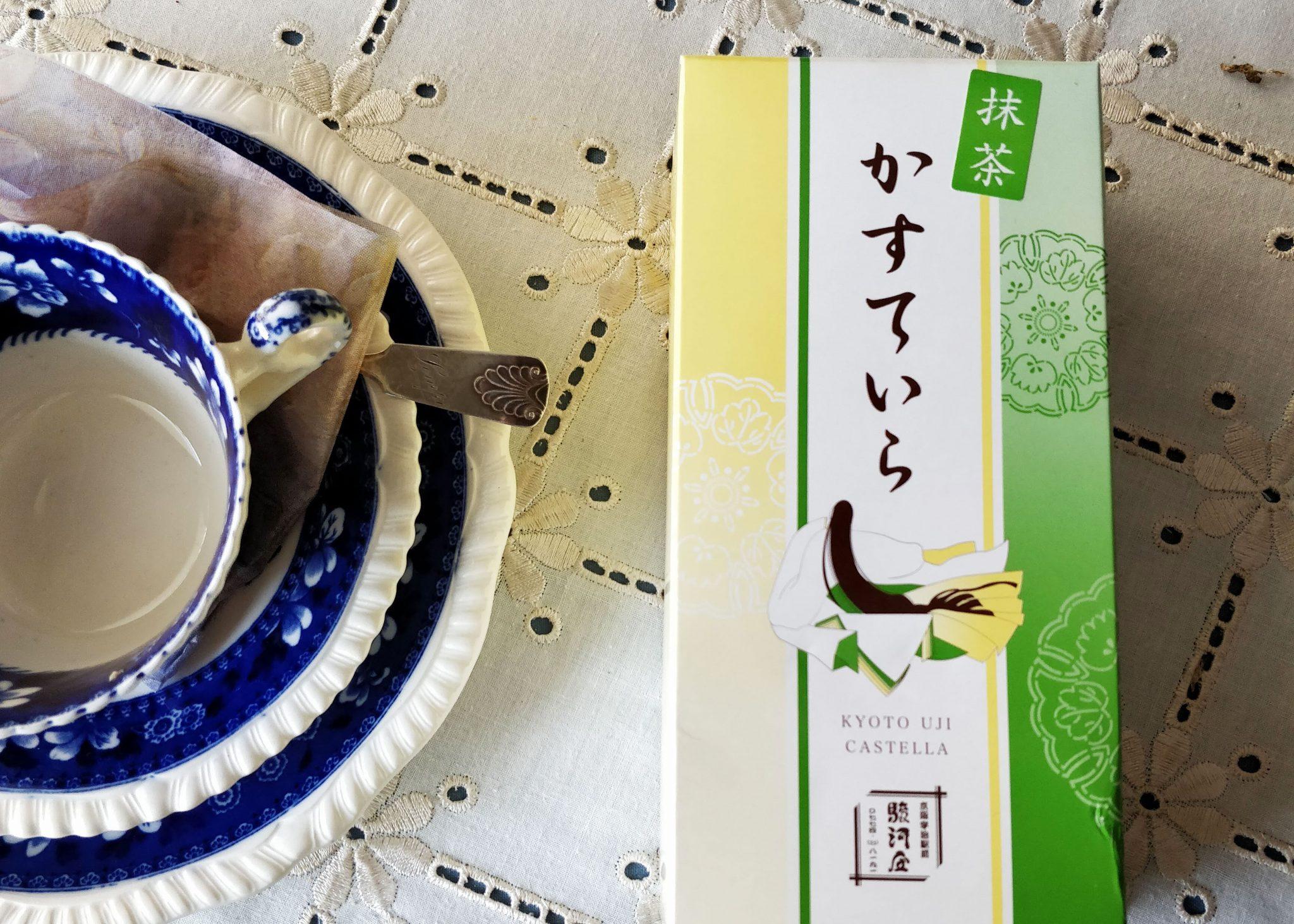 sininen teekuppi ja paketti ujista ostettua kakkua vihreä-keltaisessa paketissa jossa lukee hiraganalla kasuteira