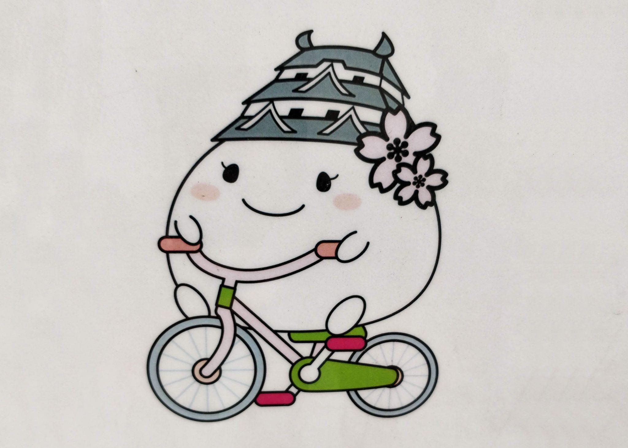 Pyöräilevä Himejin maskotti, joka on vaalea pallo jolla on linna päässä