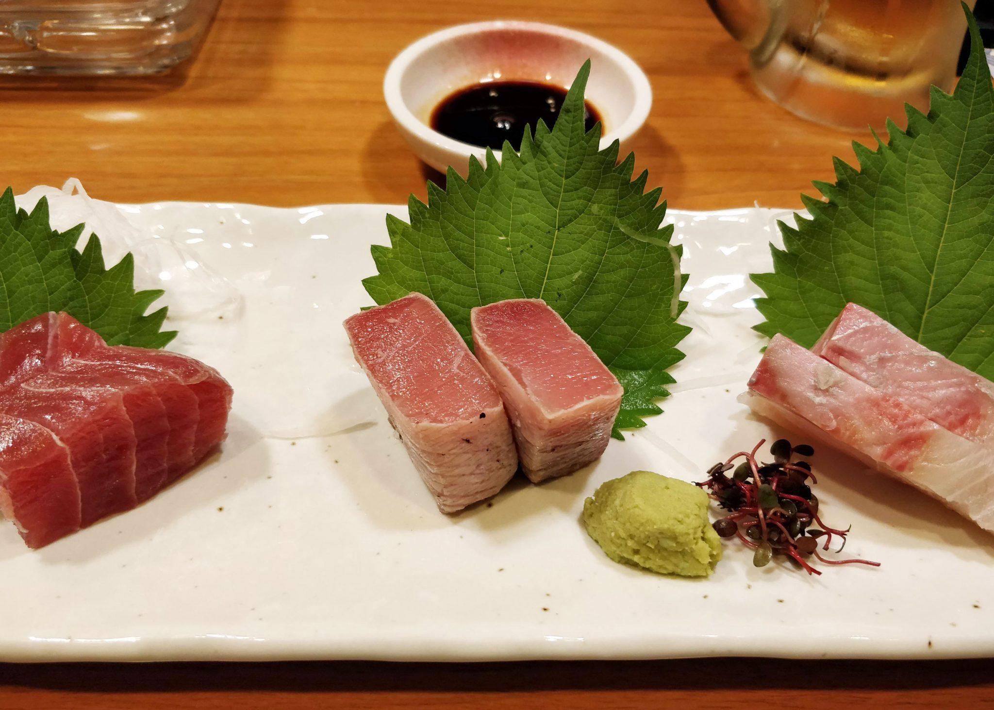 sashimi-annos japanissa, raakaa kalaa, koristelehtiä ja wasabia