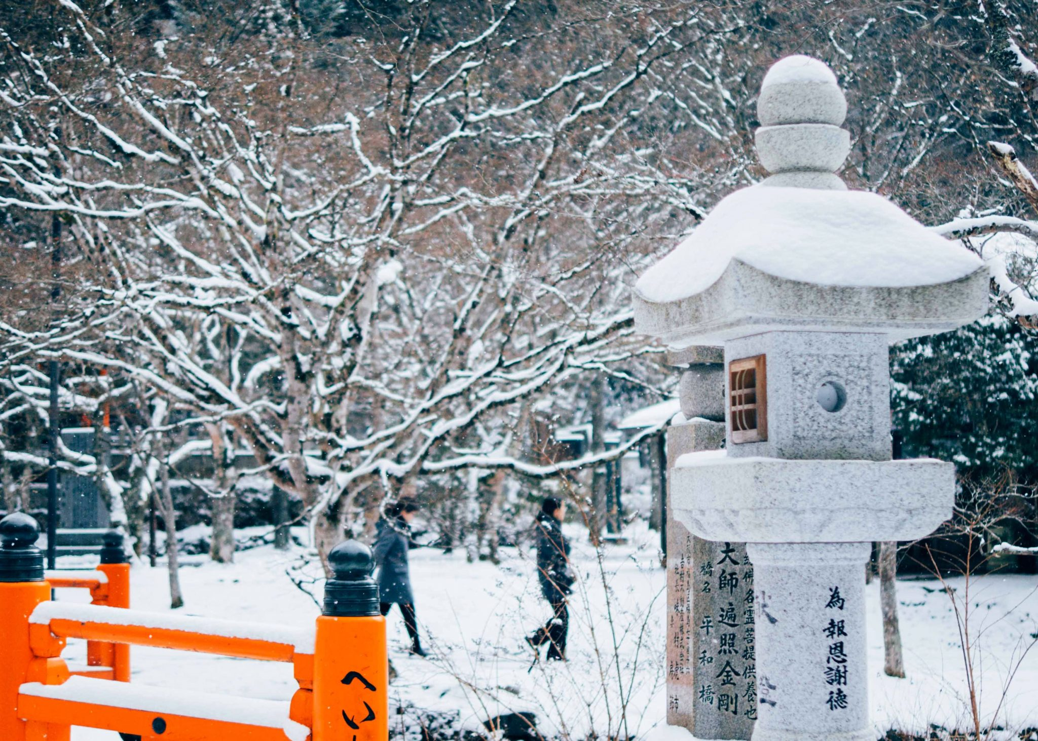 temppelin lyhty talvella Japanissa, lunta puita ja ihmisiä kävelemässä