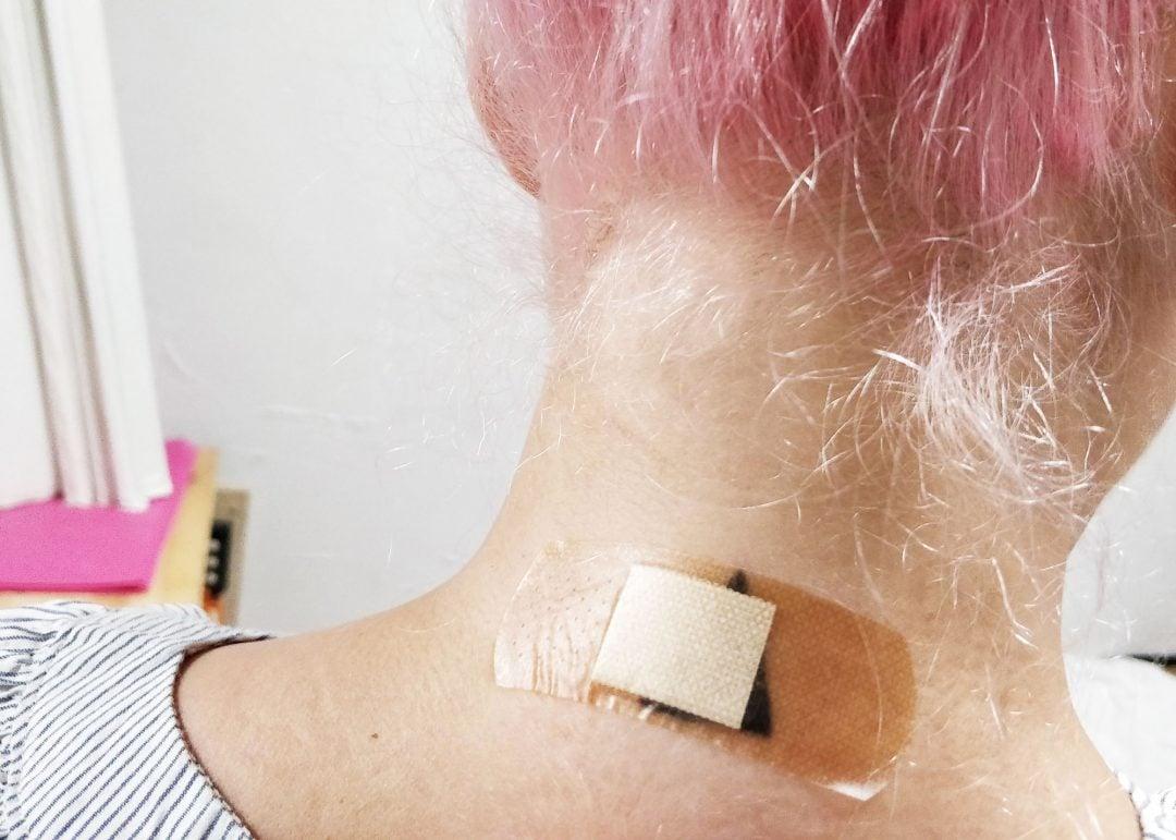Niska, jossa on tatuoitu kolmio, joka on peitetty läpinäkyvällä laastarilla.