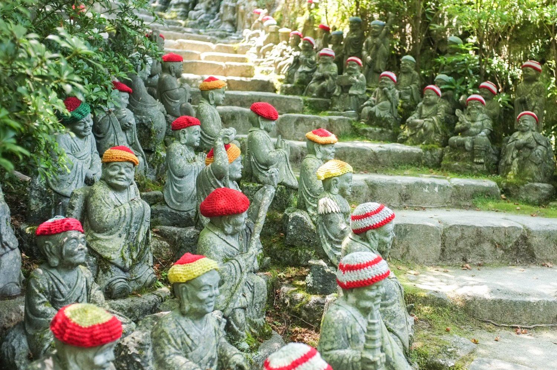 temppelin pieni buddha-patsaita, joiden päässä on hatut
