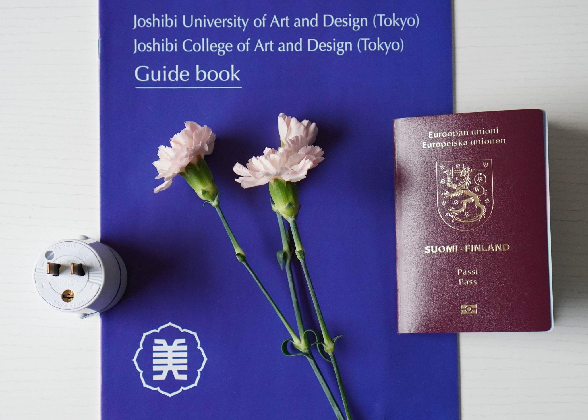 asetelma, jossa on vaihtokoulun esite, passi ja japanin adapteri