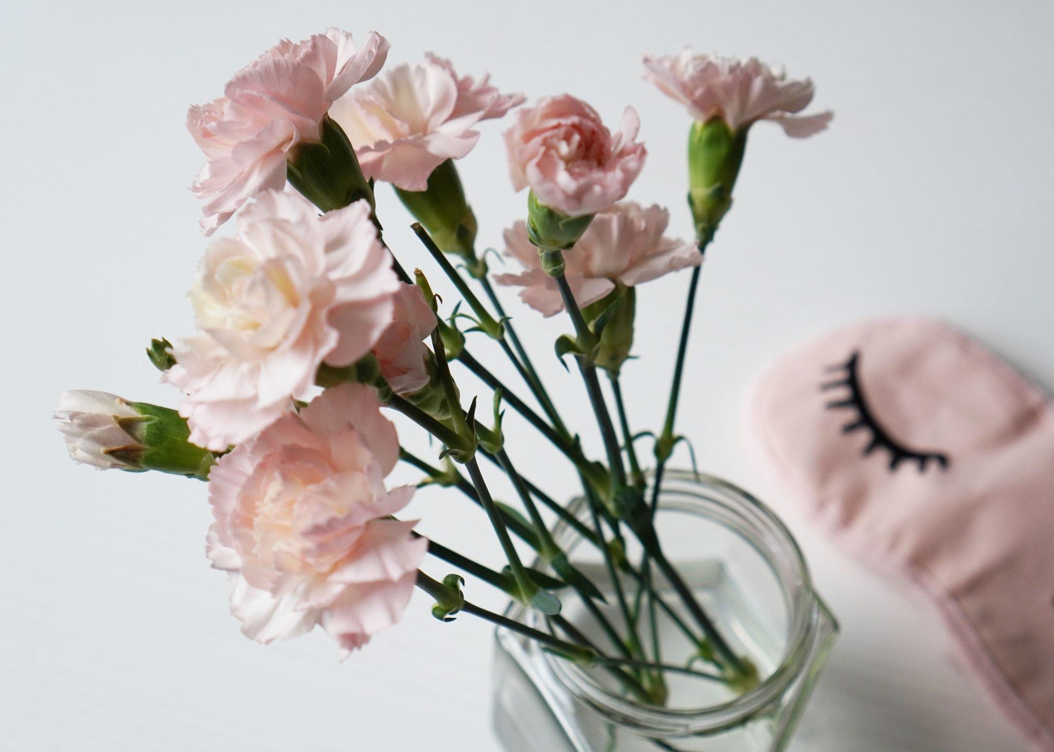 vaaleanpunaisia neilikkoja ja unimaski