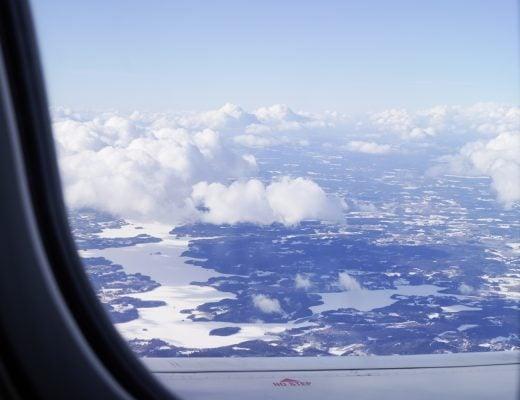 maisema koneen ikkunasta: pilviä, metsää ja lunta