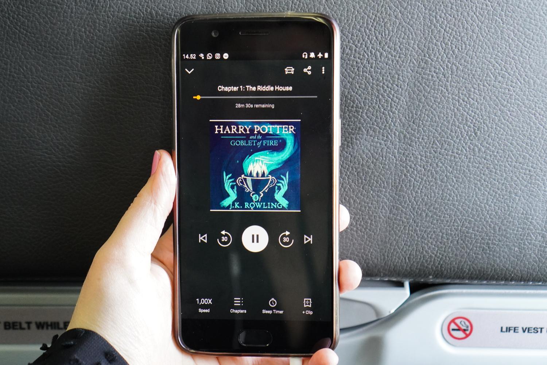 lentokoneessa käsi pitelee puhelinta, jossa on Harry Potter-äänikirja