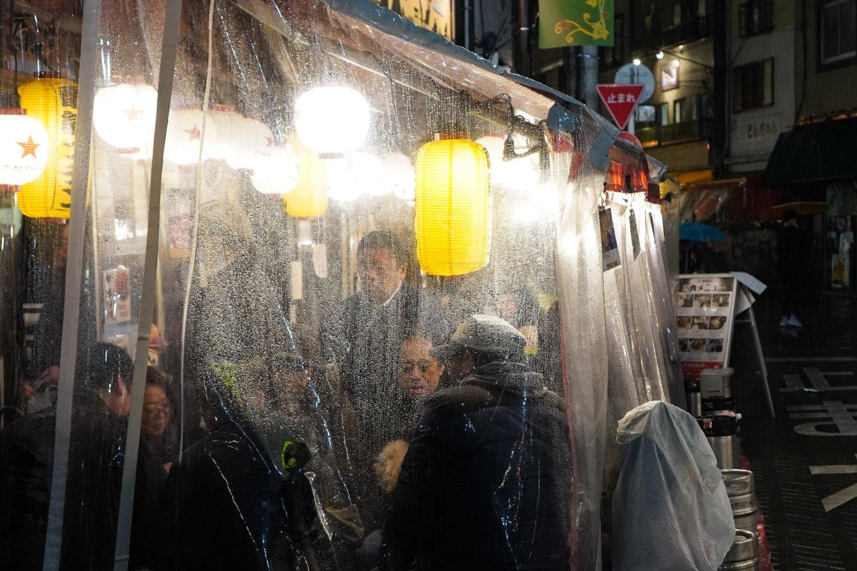 sateella ihmisiä muoviverhon takana syömässä