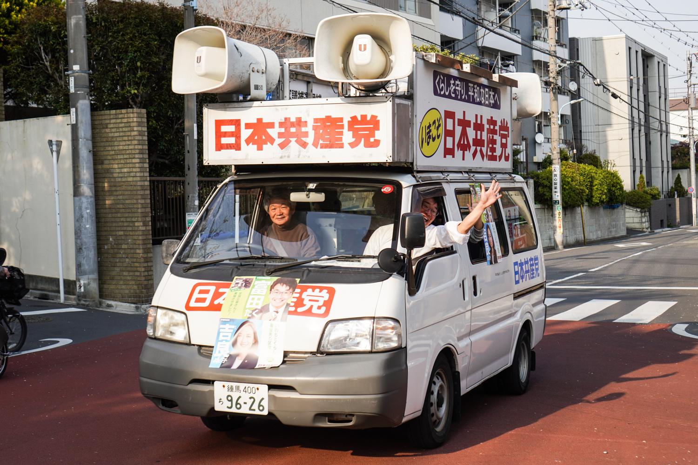 japanilaista vaalimainontaa: mies vilkuttaa kovaäänisauton ikkunasta