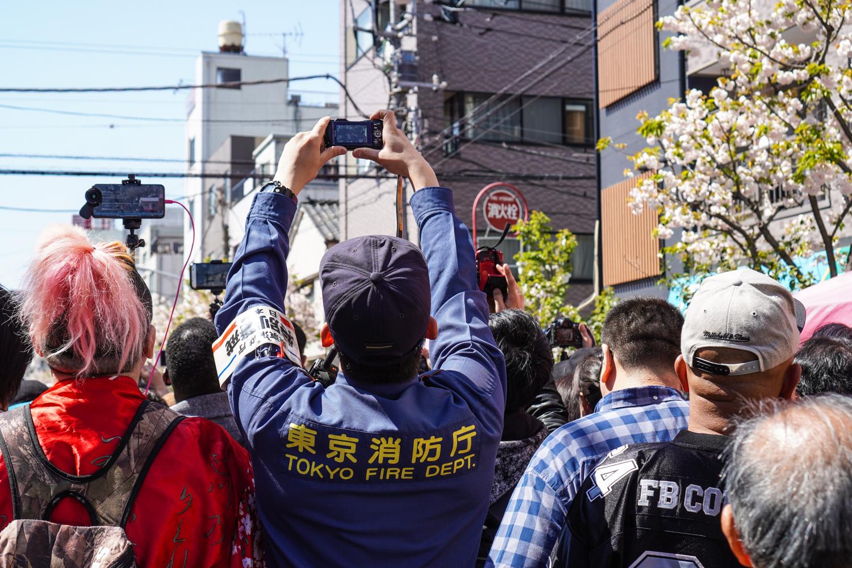 ihmisiä yrittämässä saada kuvaa kulkueesta, mukana Tokion palomies!