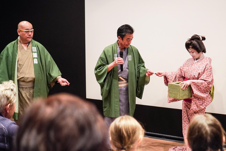 Geisha ojentaa arvontalappua