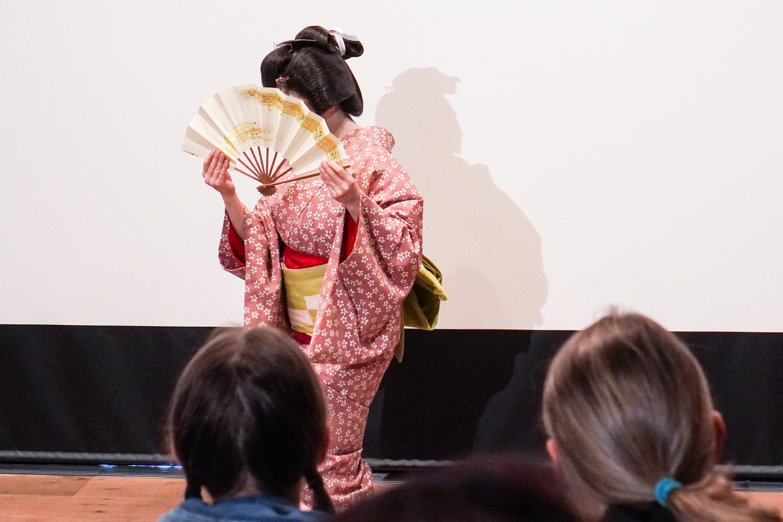 tanssiva geisha piiloutuu viuhkan taakse