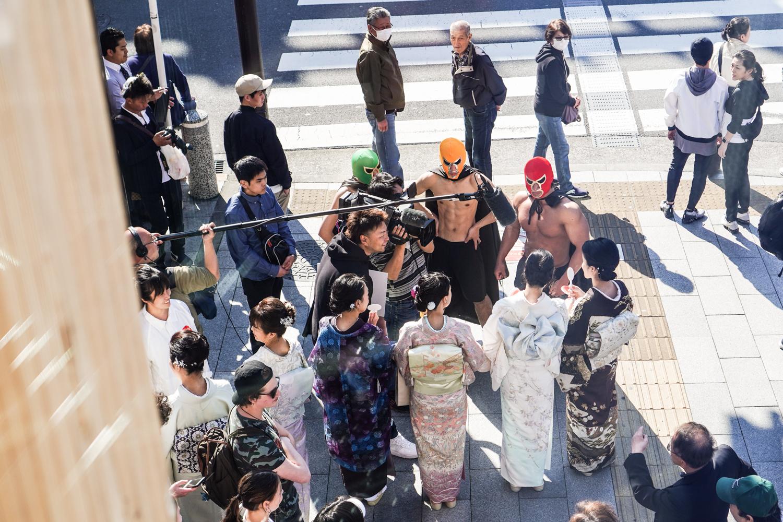 paikallinen televisioryhmä haastattelee kimonoon pukeutuneita naisia. seurassa paidattomia painijamaskisia miehiä
