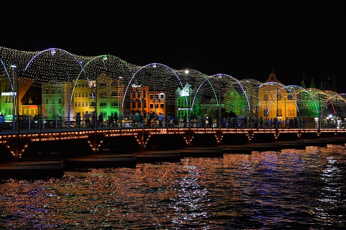 Iltaisin niin värikkäät talot kuin Queen Emma Bridge on valaistuna.