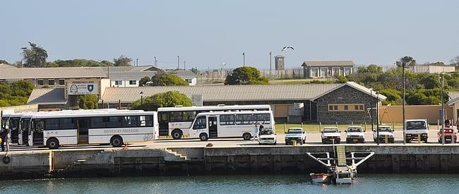 Linja-autot valmiina saarikierrokselle laiturin edessä - taustalla itse vankila