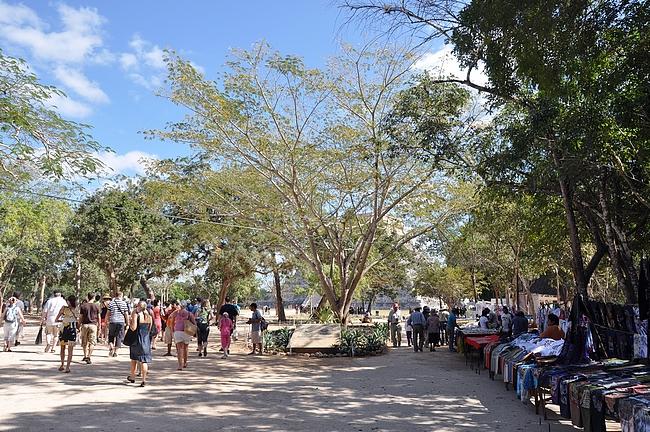 Kukulcánin temppeli siintää taustalla, kun kaupustelijoiden reunustamaa tietä pitkin lähestytään aluetta.