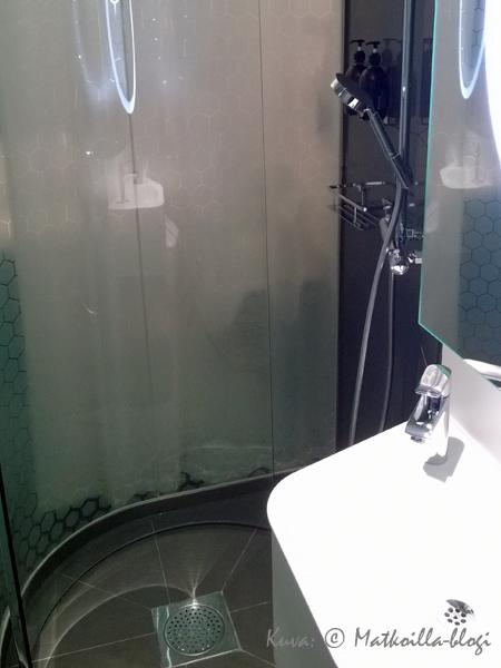 Kylpyhuoneen suihkunurkkaus on lasiseinäinen huoneen suuntaan, verho löytyy kuitenkin ulkopouolella. Kuva: © Matkoilla-blogi