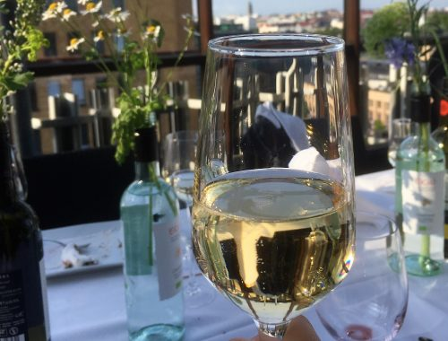 viinilasi kesäisesti katetun pöydän yllä
