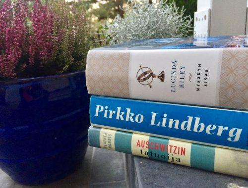 Kolmen kirjan nidepuolet kanervan vieressä