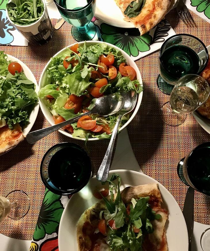 salaattia, pizzaa ja viiniä pöydällä