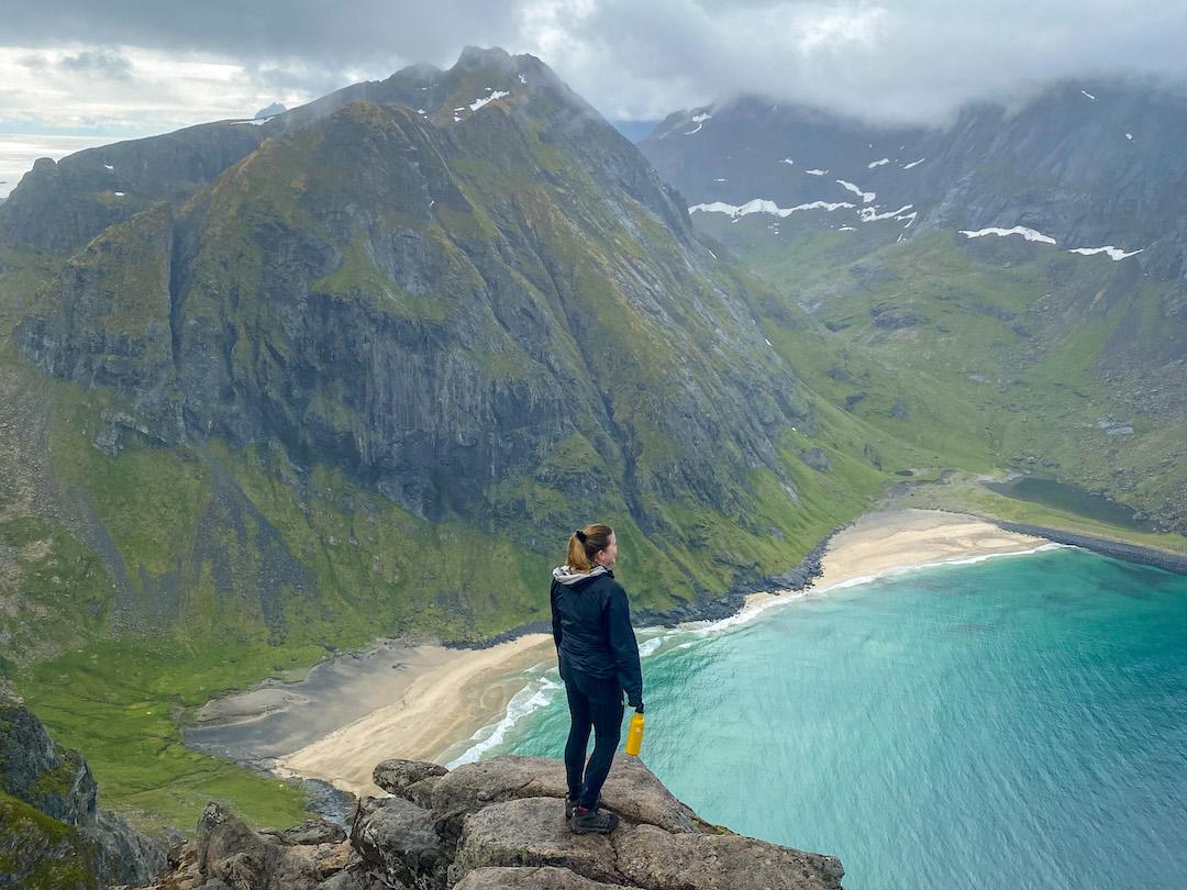 Nainen seisoo korkealla kalliolla, taustalla ranta ja vuoria