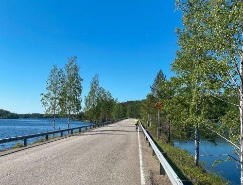 pyöräilijä puumalan saaristoreitillä, tien molemmin puolin järvi