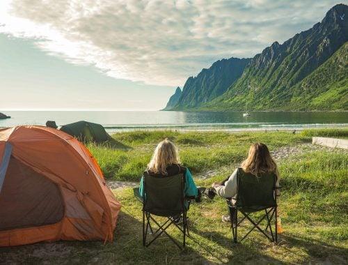 kaksi naista istuu retkituoleissa rannalla, taustalla vuori