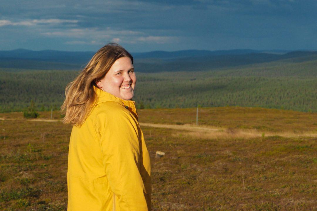 Lähikuva naisesta keltaisessa takissa, taustalla Saariselän tunturit