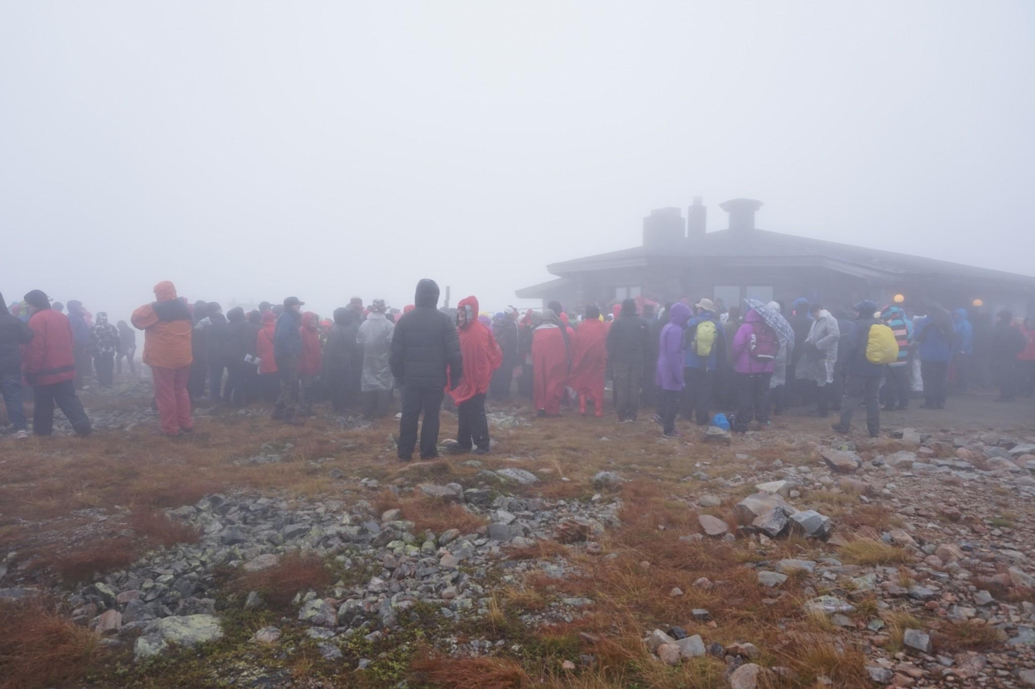 Ylläksen huipulla kuoroja kuunteli sadetakein varustautunut joukko.