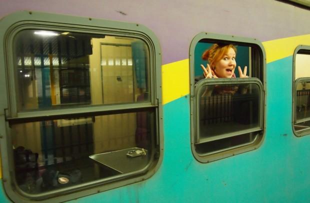Iloinen matkustaja junassa.