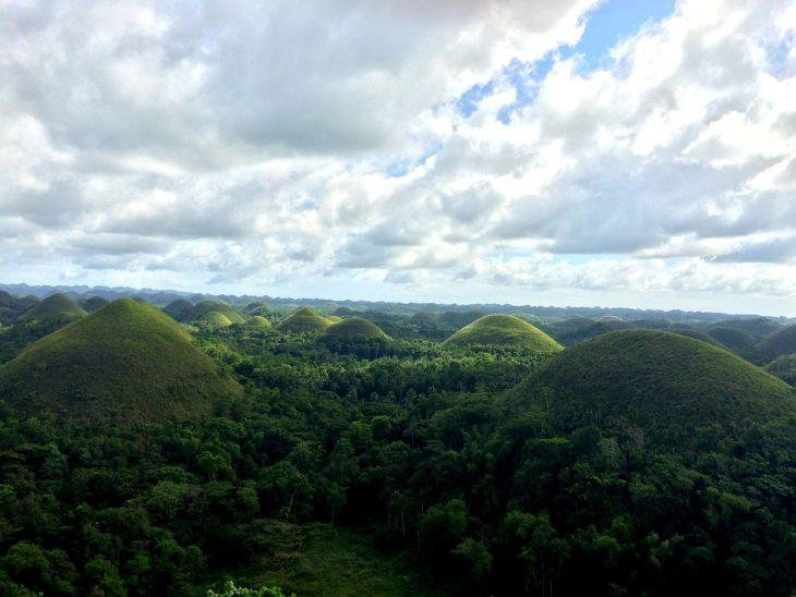 Satoja vihreitä kukkuloita horisontissa ja pilvinen taivas.