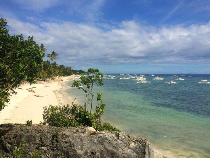 Ranta Filippiineillä, valkoista rantahiekkaa ja palmupuita. Turkoosi meri.