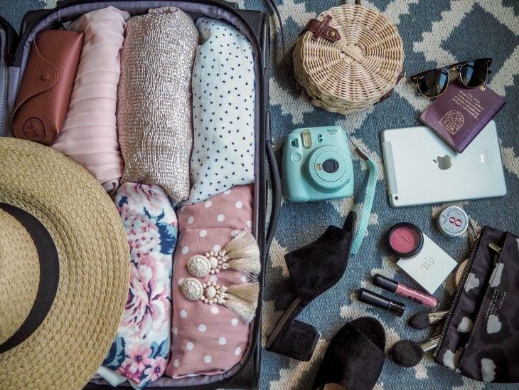 matkalaukku täynnä vaatteita, lattialla kamera, passi, laukku ja meikkeja