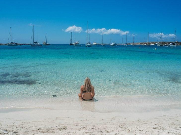 tyttö istuu valkohiekkaisella rannalla turkoosissa meressä