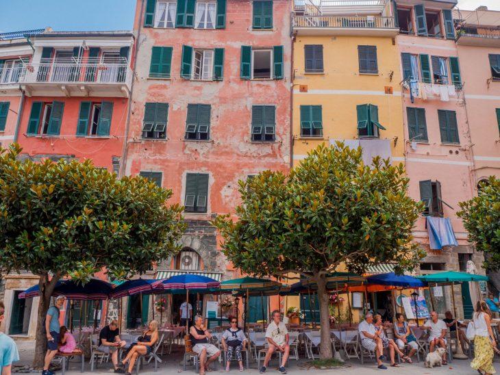 ihmiset istuvat terassilla pienellä aukiolla italiassa