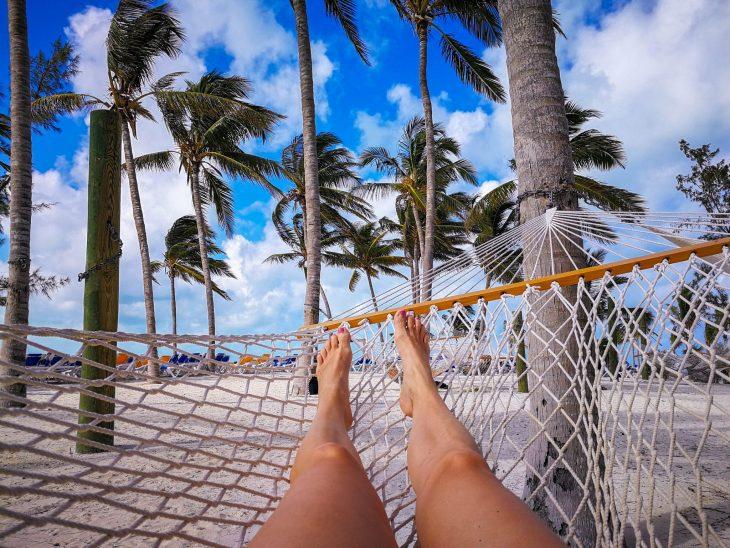 Jalat riippukeinussa palmupuut taustalla
