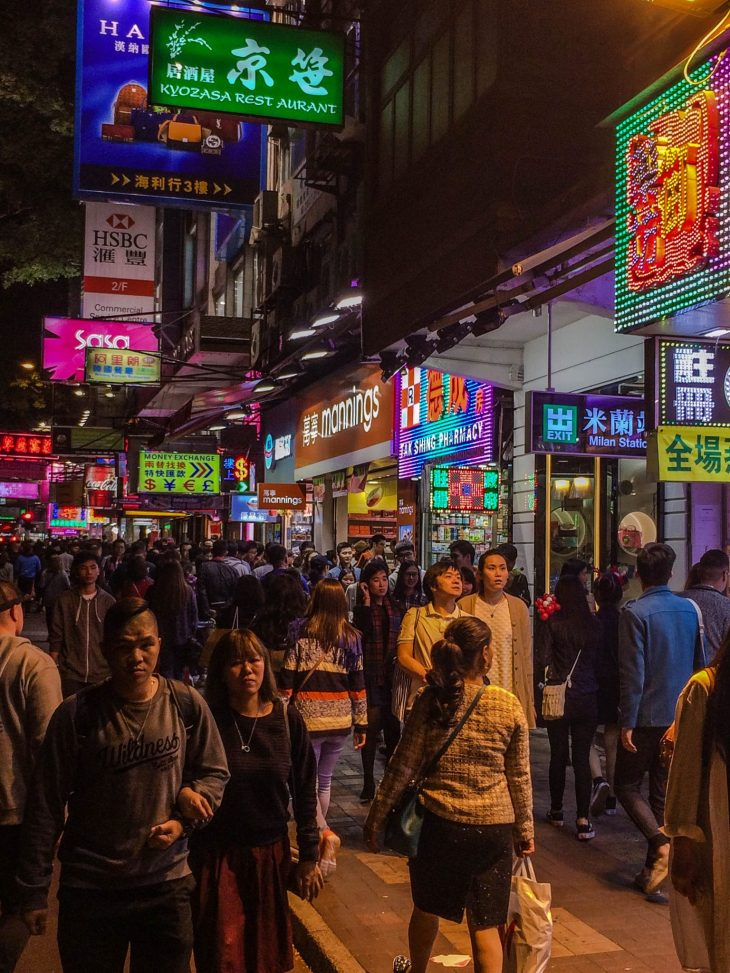 katu täynnä ihmisiä kiinassa, paljon neon värisiä valokylttejä