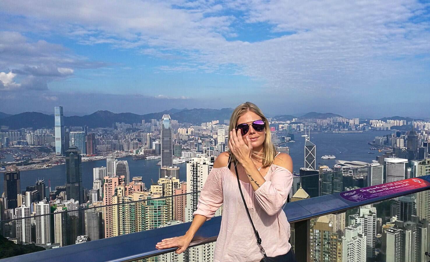 tyttö poseeraa kameralle hong kong pilvenpiirtäjät taustalla.