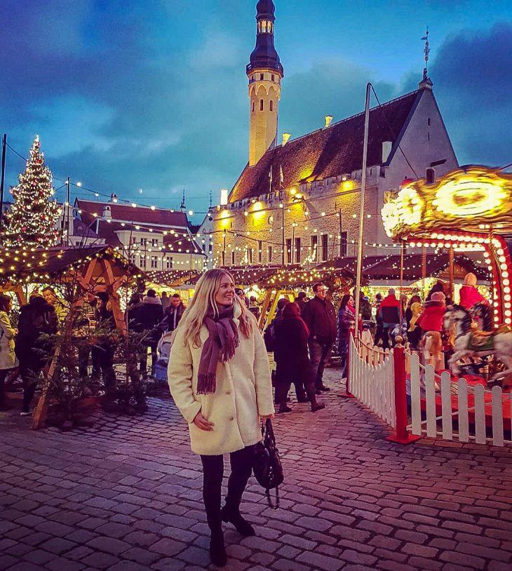 nainen seisoo joulumarkkinoilla ja taustalla on karuselli ja joulukuusi