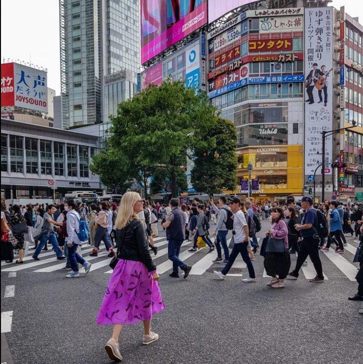 nainen kävelee ruuhkaisen risteyksen yli tokiossa