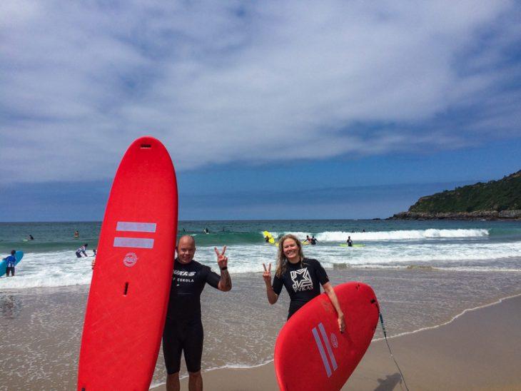 mies ja nainen surffilaudat kainalossa poseeraavat kameralle