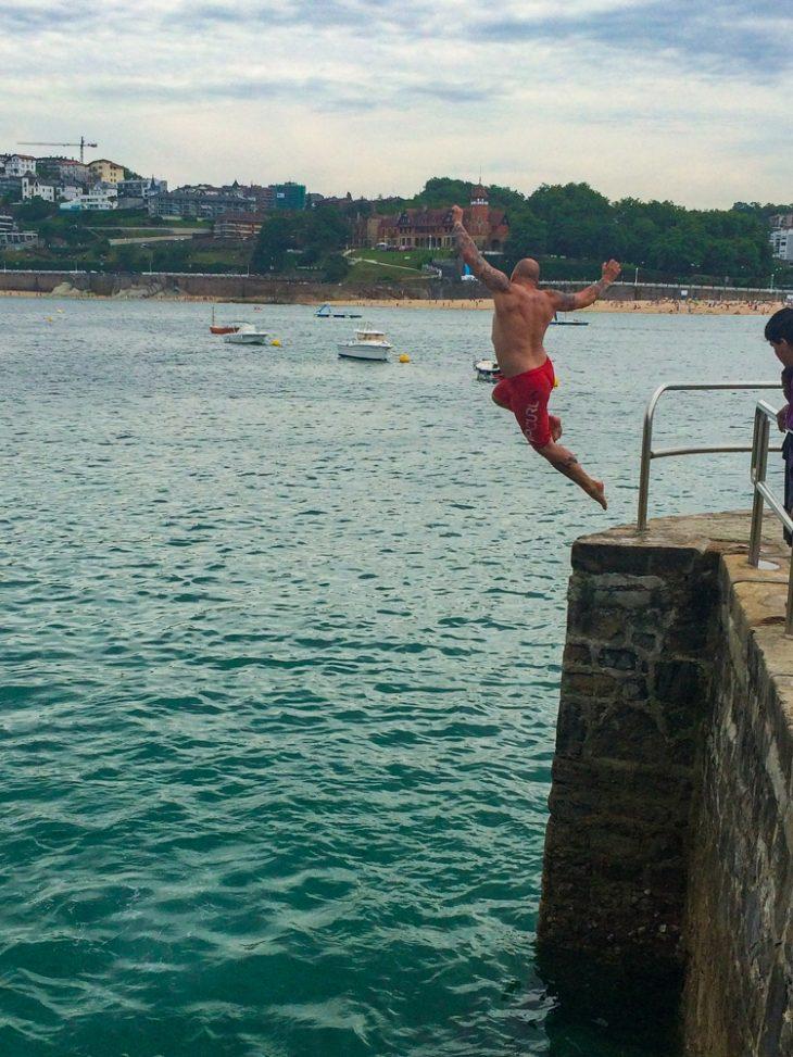 mies hyppää sillalta uimaan