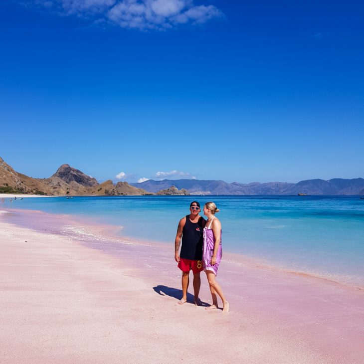 man and woman standing in a pink beach